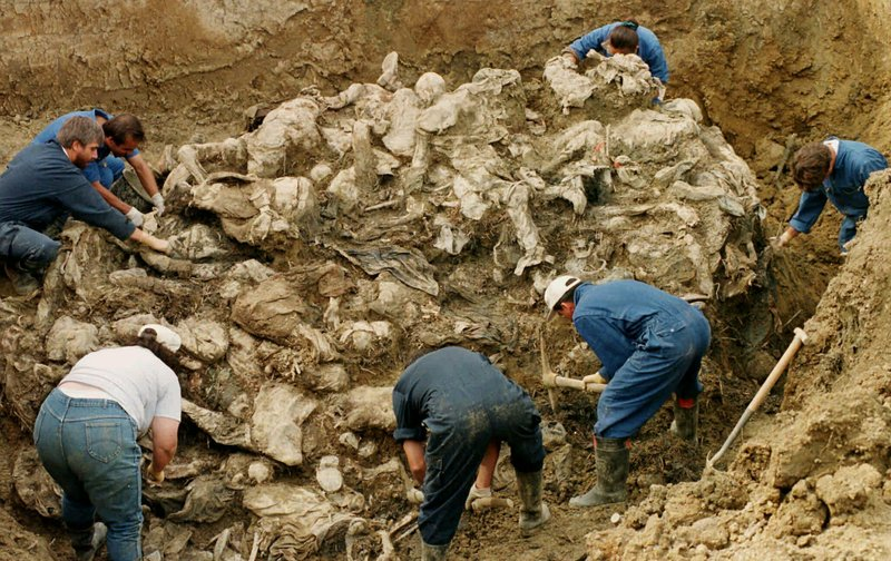FILE - In this Sept. 18, 1996 file photo, International War Crimes Tribunal investigators clear away soil and debris from dozens of Srebrenica victims buried in a mass grave near the village of Pilica, north east of Tuzla, Boisnia-Herzegovina. (AP Photo/Staton R. Winter, File)