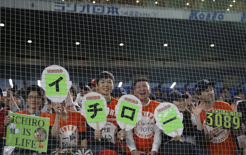 Fans of Seattle Mariners right fielder Ichiro Suzuki cheer with banners reading