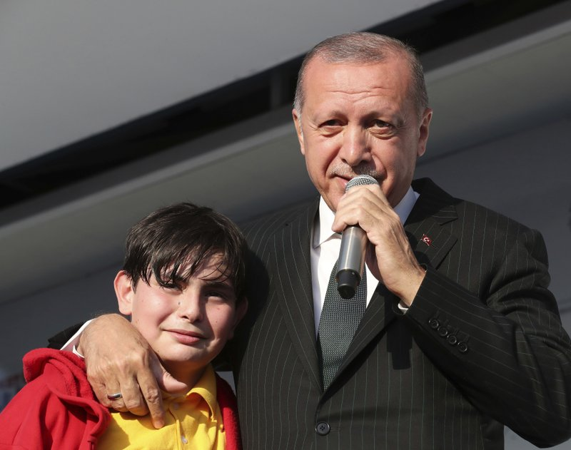 Turkey's President Recep Tayyip Erdogan reacts with a young boy as he addresses the supporters of his ruling Justice and Development Party during a rally in Kocaeli, Turkey, Tuesday, March 19, 2019. (Presidential Press Service via AP, Pool)
