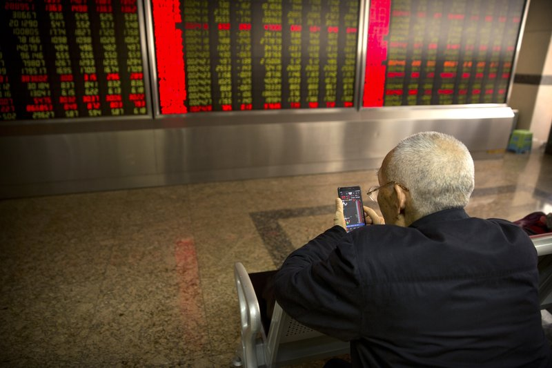 A Chinese investor uses his smartphone as he monitors stock prices at a brokerage house in Beijing, Wednesday, March 20, 2019. (AP Photo/Mark Schiefelbein)