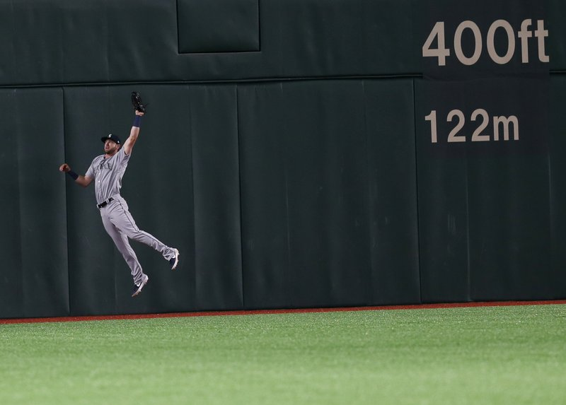 Seattle Mariners center fielder Mitch Haniger jumps to catch a fly ball hit by Oakland Athletics' Stephen Piscotty in the seventh inning of Game 1 of their Major League opening series baseball game at Tokyo Dome in Tokyo, Wednesday, March 20, 2019. (AP Photo/Toru Takahashi)