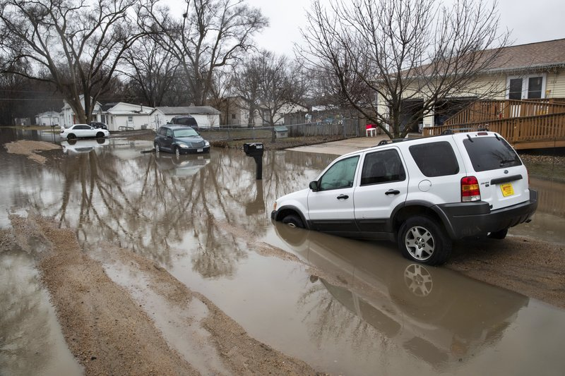 Cars are stuck in floodwaters Tuesday, March 19, 2019, in Fremont, Neb. Flooding is expected throughout the week in several states as high water levels flow down the Missouri River. (Brendan Sullivan/Omaha World-Herald via AP)
