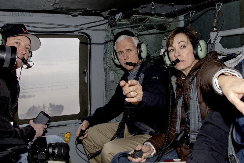 Vice President Mike Pence and Iowa Gov. Kim Reynolds, second right point to flooded areas, with Neb. Gov. (AP Photo/Nati Harnik)