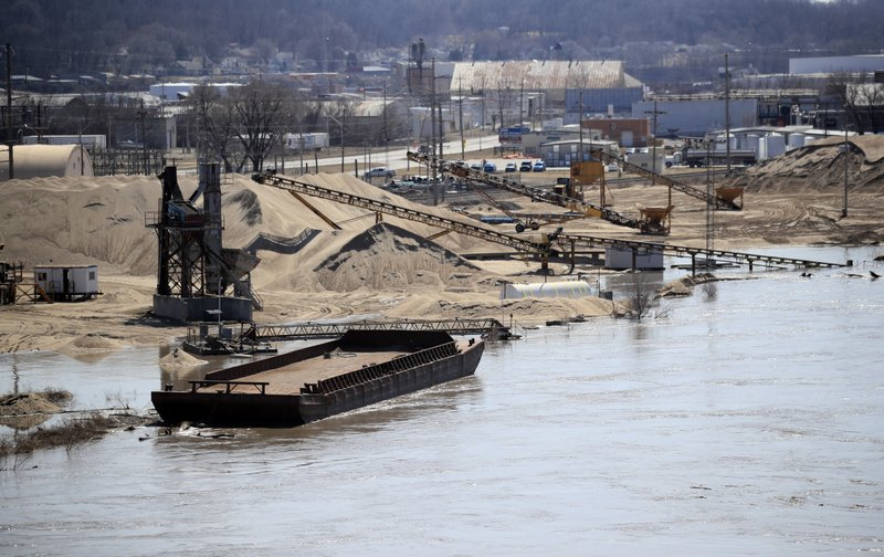 A barge is moored along the Missouri River as floodwaters begin to creep into a dredge operation in St Joseph, Mo. (AP Photo/Orlin Wagner)