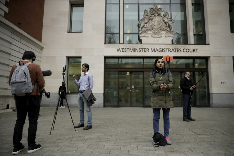 Members of the media report from outside Westminster Magistrates Court in London, shortly after fugitive Indian diamond tycoon Nirav Modi was denied bail in a hearing, Wednesday, March 20, 2019. (AP Photo/Matt Dunham)