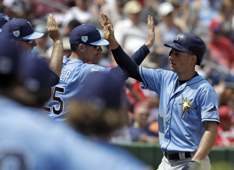 Tampa Bay Rays' Brandon Lowe, right, high fives teammates after scoring on a two-run single by Willy Adames off Philadelphia Phillies pitcher Vince Velasquez during the second inning of a spring training baseball game Monday, March 11, 2019, in Clearwater, Fla. (AP Photo/Chris O'Meara)