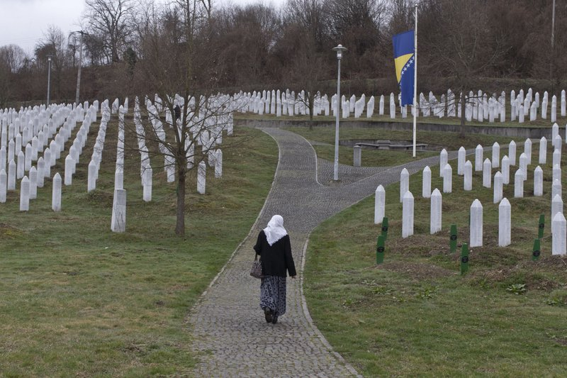 A woman walks through the cemetery of the Potocari memorial center for victims of the Srebrenica genocide in Potocari, Bosnia and Herzegovina, Wednesday, March 20, 2019. (AP Photo/Marko Drobnjakovic)