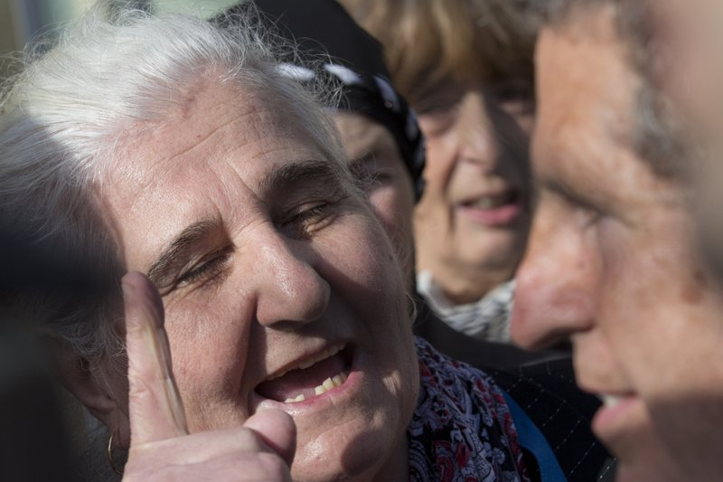 Munira Subasic of the Mothers of Srebrenica, left, haggles Peter Robinson of the U.S., lawyer for former Bosnian Serb leader Radovan Karadzic, after the court upheld Karadzic's conviction at International Residual Mechanism for Criminal Tribunals in The Hague, Netherlands, Wednesday, March 20, 2019. (AP Photo/Peter Dejongl)