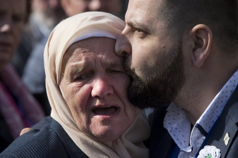 A crying woman with the Mothers of Srebrenica is hugged after the court upheld the convictions of former Bosnian Serb leader Radovan Karadzic at International Residual Mechanism for Criminal Tribunals in The Hague, Netherlands, Wednesday, March 20, 2019. (AP Photo/Peter Dejongl)