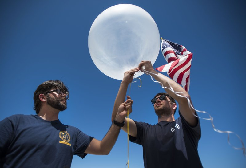 In this March 13, 2019 photo, Project OWL team leader Bryan Knouse ties a U.S. flag to a helium-filled balloon carrying a tiny transmitter, aided by D. (AP Photo/Carlos Giusti)