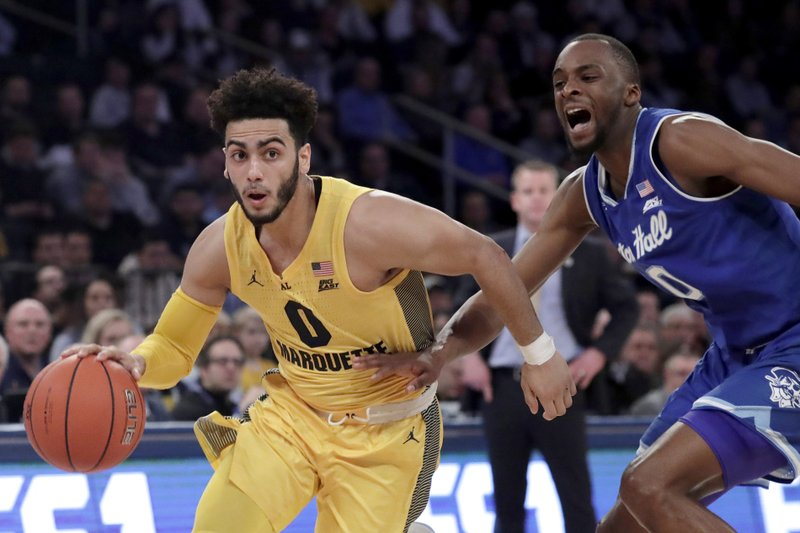 FILE - In this Friday, March 15, 2019, file photo, Marquette guard Markus Howard (0) drives past Seton Hall guard Quincy McKnight (0) during the first half of an NCAA college basketball in the Big East Conference tournament in New York. (AP Photo/Julio Cortez, File)