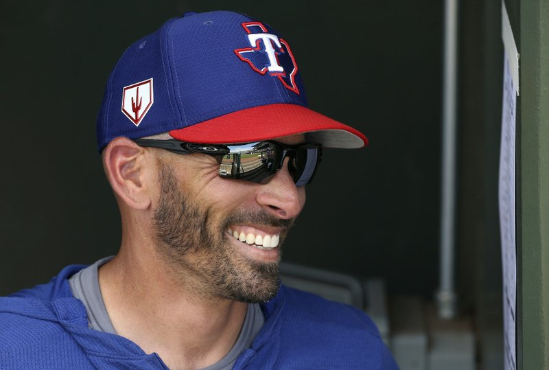 FILE - In this March 6, 2019, file photo, Texas Rangers manager Chris Woodward smiles as he talks with other coaches prior to a spring training baseball game against the San Francisco Giants in Surprise, Ariz. (AP Photo/Ross D. Franklin, File)