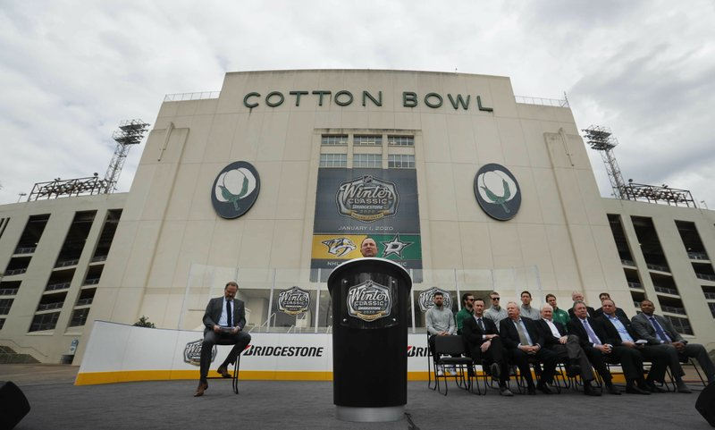 NHL commissioner Gary Bettman speaks from the podium with others looking on during a news conference outside the Cotton Bowl in Dallas, Wednesday, March 20, 2019. (AP Photo/LM Otero)
