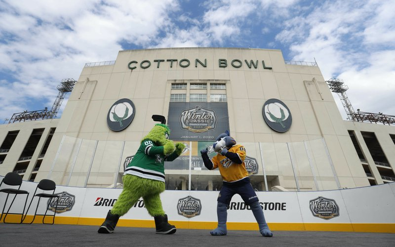 Mascots for the Nashville Predators, right, and the Dallas Stars pose for a photo in front of the Cotton Bowl in Dallas, Wednesday, March 20, 2019. (AP Photo/LM Otero)
