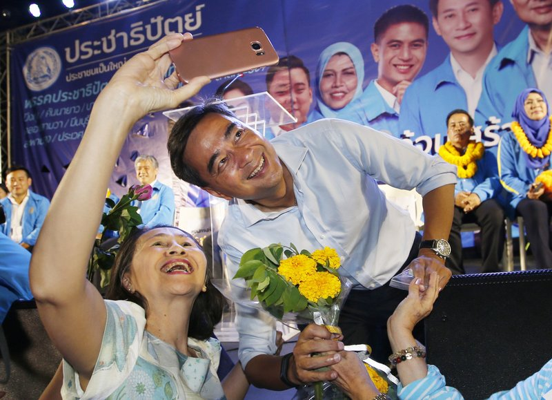 In this Monday, March 18, 2019. a supporter takes a selfie with the leader of Thailand's Democrat Party Abhisit Vejjajiva during an election campaign in Bangkok, Thailand. (AP Photo/Sakchai Lalit)
