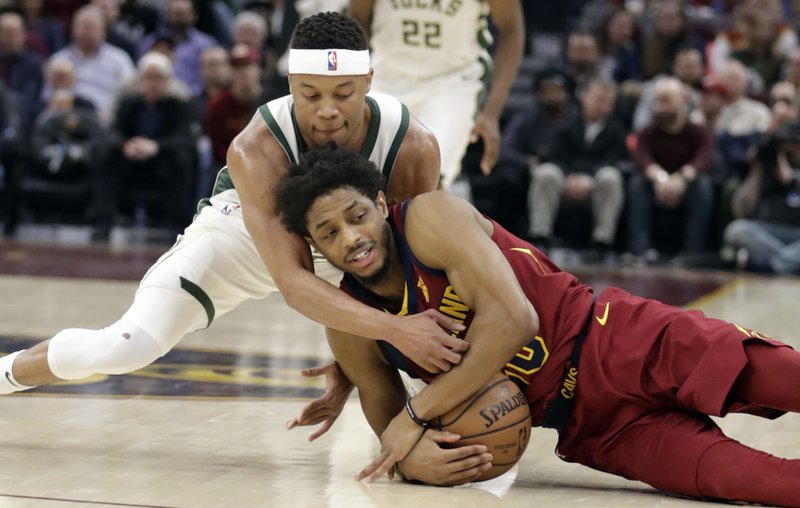 Milwaukee Bucks' Tim Frazier, top, and Cleveland Cavaliers' Brandon Knight scramble for the ball during the first half of an NBA basketball game Wednesday, March 20, 2019, in Cleveland. (AP Photo/Tony Dejak)