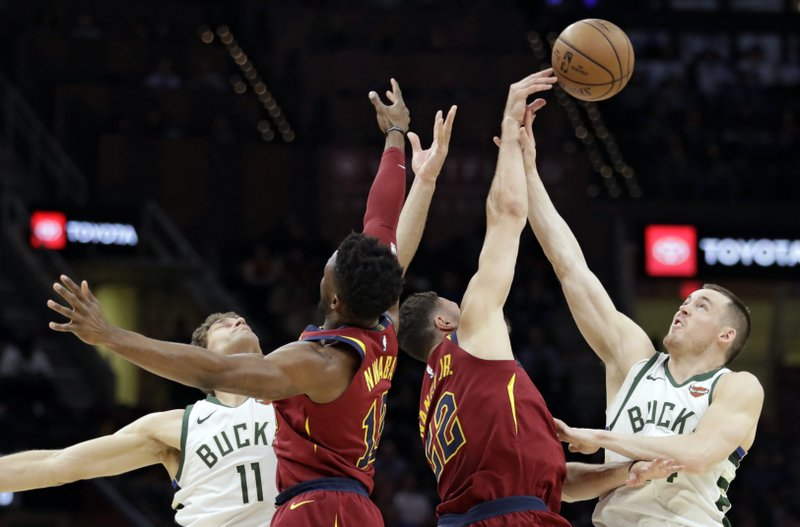 Milwaukee Bucks' Pat Connaughton, right, Cleveland Cavaliers' Larry Nance Jr. and David Nwaba, and Bucks' Brook Lopez, left, reach for the ball during the first half of an NBA basketball game Wednesday, March 20, 2019, in Cleveland. (AP Photo/Tony Dejak)