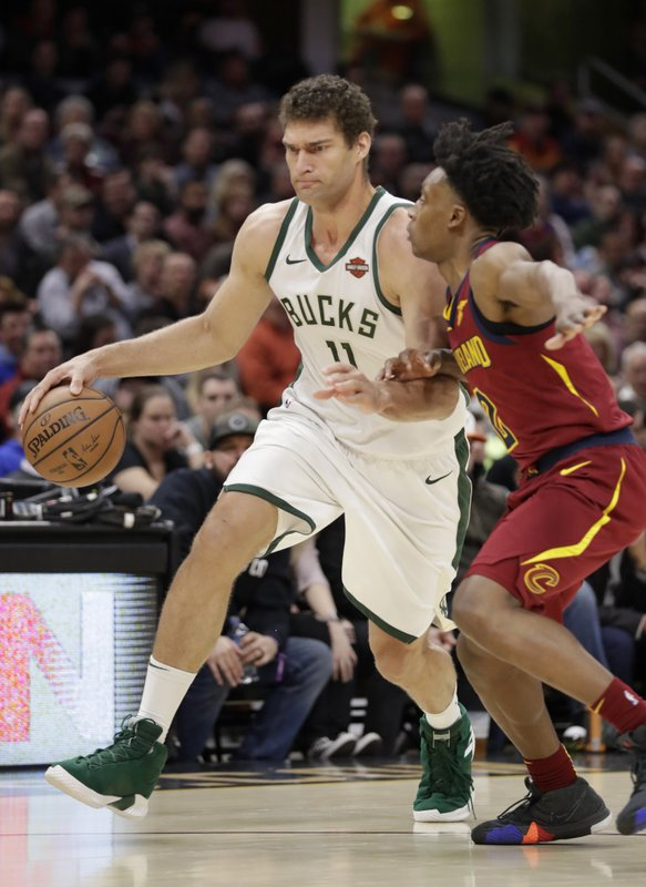 Milwaukee Bucks' Brook Lopez (11) drives past Cleveland Cavaliers' Collin Sexton (2) during the first half of an NBA basketball game Wednesday, March 20, 2019, in Cleveland. (AP Photo/Tony Dejak)