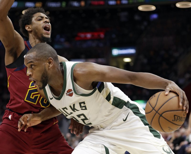 Milwaukee Bucks' Khris Middleton (22) drives past Cleveland Cavaliers' Brandon Knight during the first half of an NBA basketball game Wednesday, March 20, 2019, in Cleveland. (AP Photo/Tony Dejak)