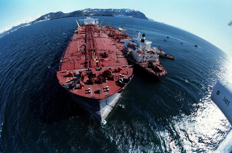 FILE - In this April 4, 1989, file photo, the grounded tanker Exxon Valdez, left, unloads oil onto a smaller tanker, San Francisco, as efforts to refloat the ship continue on Prince William Sound. (AP Photo/Rob Stapleton, File)