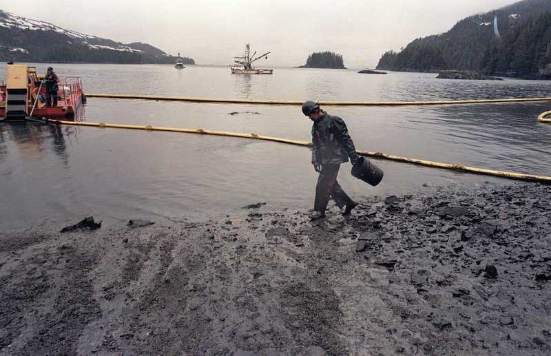 FILE - In this April 17, 1989, file photo, a worker makes his way across the polluted shore of Block Island, Alaska, as efforts are underway to test techniques to clean up the oil spill of the tanker Exxon Valdez in Prince William Sound. (AP Photo/John Gaps III, File)