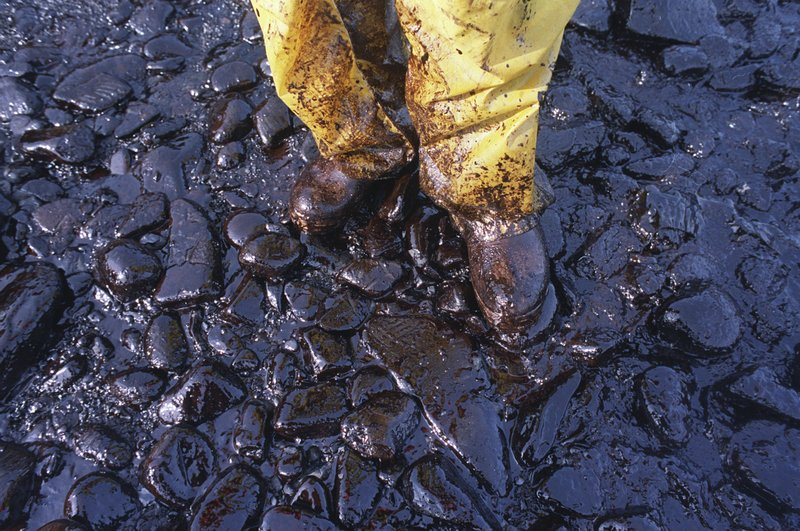 FILE - In this April 11, 1989, file photo, thick crude oil that washed up on the cobble beach of Evans Island sticks to the boots and pants of a local fisherman in Prince William Sound, Alaska. (AP Photo/John Gaps III, File)