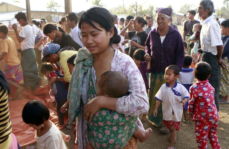 In this Wednesday, Feb. 22, 2012, photo, Myanmar refugees in Kachin State gather near their refugee camp in Myitkyina, Kachin state, northern Myanmar. (AP Photo/Khin Maung Win)