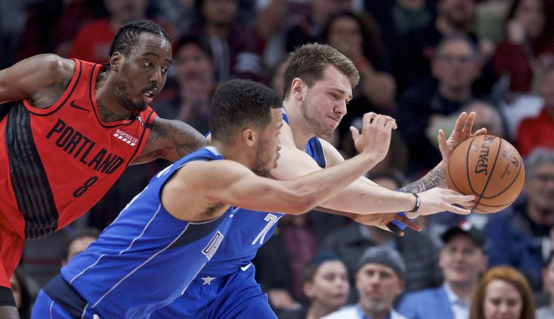 Dallas Mavericks forward Luka Doncic, right, and guard Jalen Brunson, center, reach for a loose ball in front of Portland Trail Blazers forward Al-Farouq Aminu during the first half of an NBA basketball game in Portland, Ore. (AP Photo/Craig Mitchelldyer)
