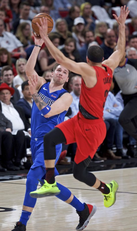 Dallas Mavericks forward Luka Doncic, left, passes the ball away from Portland Trail Blazers guard Seth Curry during the first half of an NBA basketball game in Portland, Ore. (AP Photo/Craig Mitchelldyer)