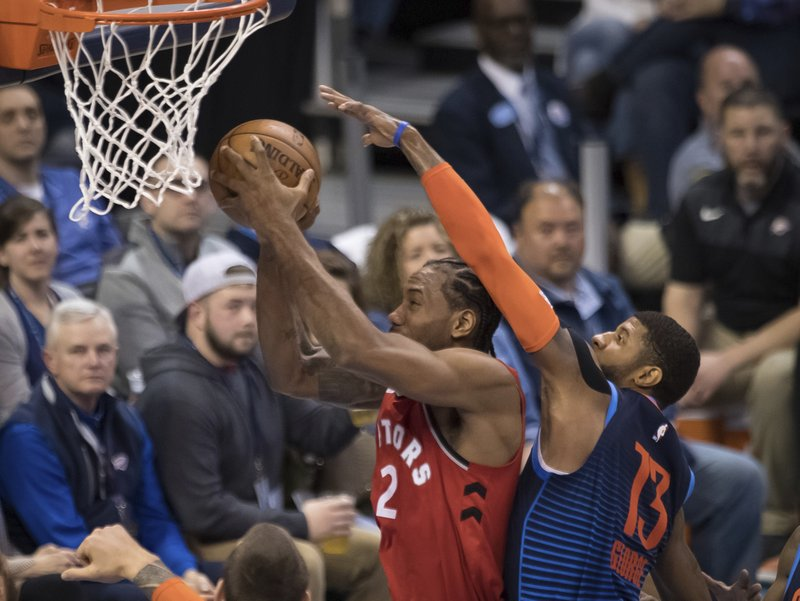 Toronto Raptors forward Kawhi Leonard (2) shoots while defended by Oklahoma City Thunder forward Paul George (13) during the first half of an NBA basketball game Wednesday, March 20, 2019, in Oklahoma City. (AP Photo/Rob Ferguson)