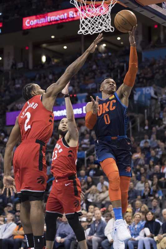 Oklahoma City Thunder guard Russell Westbrook (0) shoots past the reach of Toronto Raptors forward Kawhi Leonard (2) during the second half of an NBA basketball game Wednesday, March 20, 2019, in Oklahoma City. (AP Photo/Rob Ferguson)