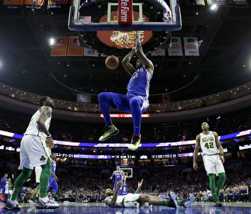 Philadelphia 76ers' Joel Embiid (21) dunks as Boston Celtics' Kyrie Irving, Marcus Morris and Al Horford, from left, watch during the second half of an NBA basketball game Wednesday, March 20, 2019, in Philadelphia. (AP Photo/Matt Slocum)