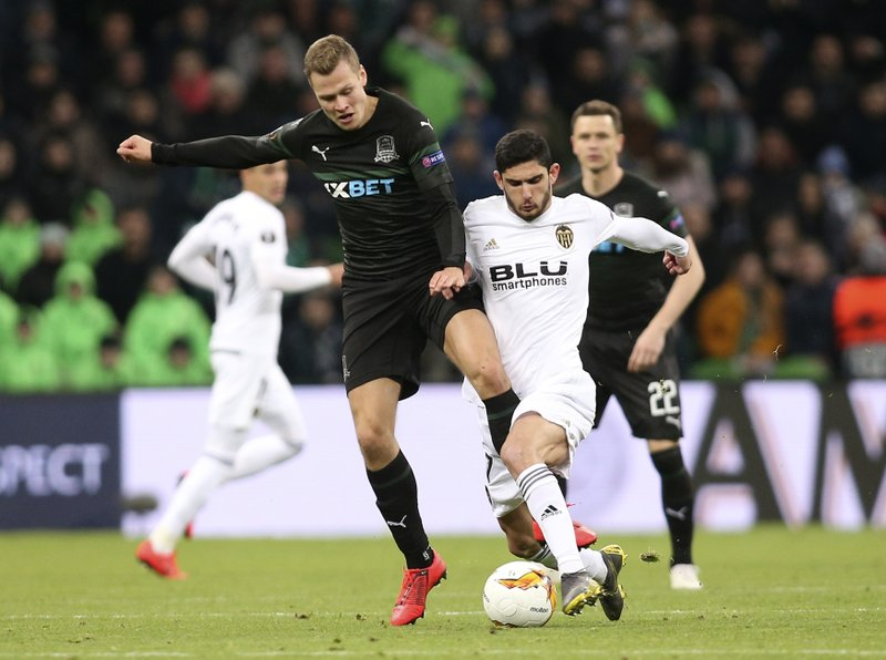Krasnodar's Dmitry Stotsky, left, and Valencia's Goncalo Guedes challenge for the ball during the Europa League round of 16, second leg soccer match between FC Krasnodar and Valencia at the Krasnodar Stadium in Krasnodar, Russia, Thursday, March 14, 2019. (AP Photo/Vitaliy Timkiv)