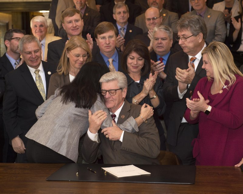 Miss. Gov. Phil Bryant hugs Miss. Sen. Angela Hill-R, Thursday, March 21, 2019 in Jackson after Bryant signed into law what is commonly known as the Heartbeat Bill in Mississippi. (Sarah Warnock/The Clarion-Ledger via AP)