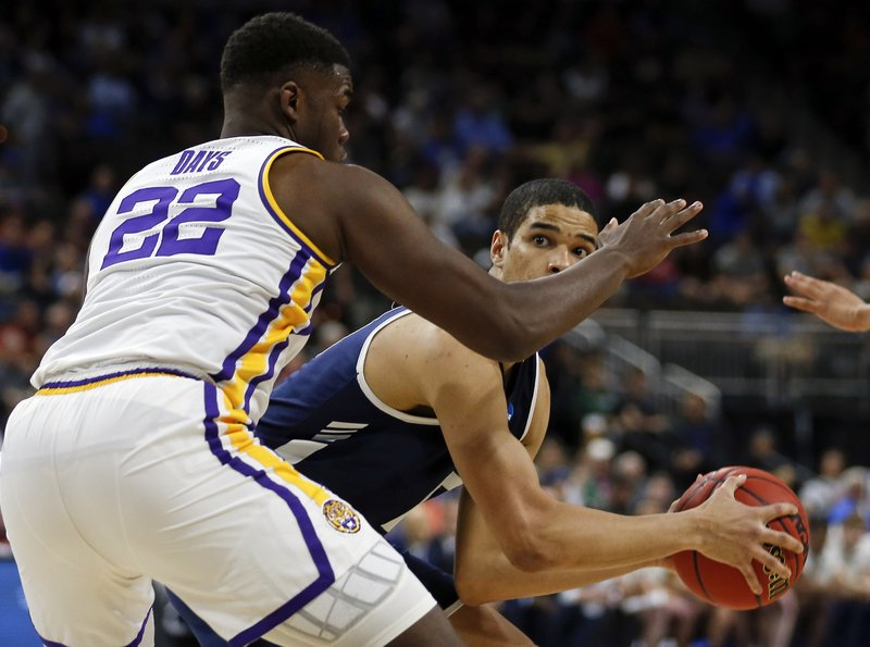 Yale 's Paul Atkinson, right, looks for a shot over LSU's Darius Days (22) during the first half of a first round men's college basketball game in the NCAA Tournament in Jacksonville, Fla. (AP Photo/Stephen B. Morton)