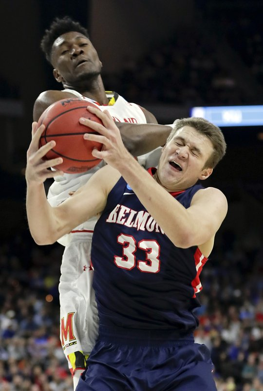 Belmont 's Nick Muszynski (33) grabs a rebound in front of Maryland 's Bruno Fernando during the first half of a first round men's college basketball game in the NCAA Tournament in Jacksonville, Fla. (AP Photo/John Raoux)