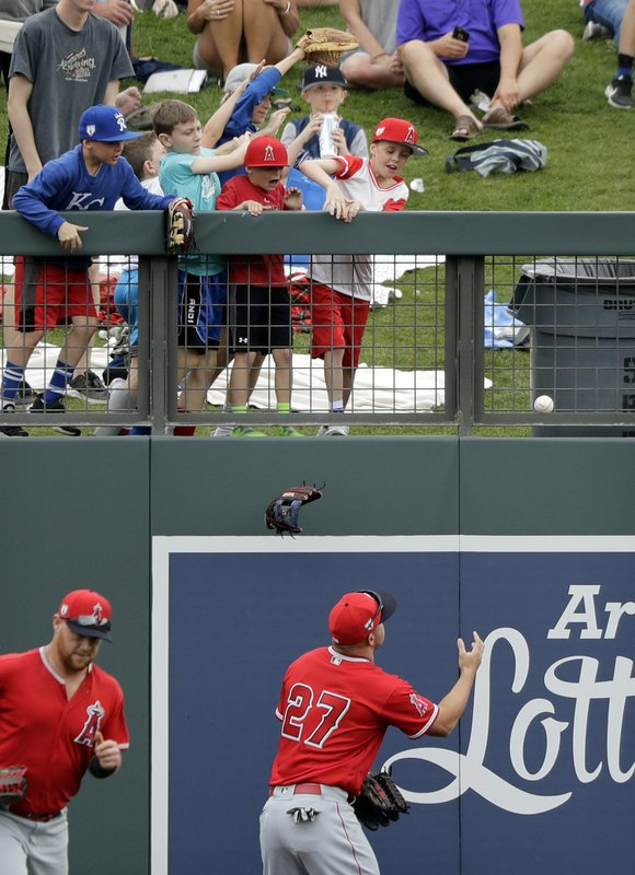 Los Angeles Angels center fielder Mike Trout (27) reaches for a ball dropped by a child that Trout had tossed to fans, while a glove falls as well, during the team's spring training baseball game against the Arizona Diamondbacks on Thursday, March 21, 2019, in Scottsdale, Ariz. (AP Photo/Elaine Thompson)