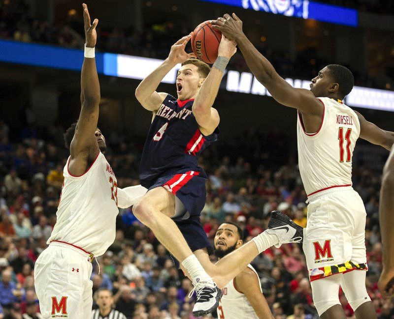 Belmont 's Dylan Windler, center, goes to the basket between Maryland 's Bruno Fernando, left, and Darryl Morsell (11) during the second half of the first round men's college basketball game in the NCAA Tournament in Jacksonville, Fla. (AP Photo/Stephen B. Morton)