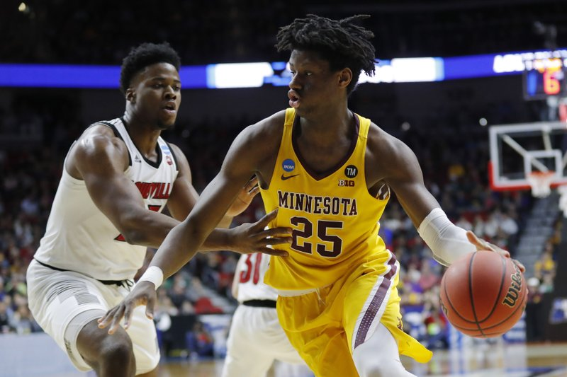 Minnesota center Daniel Oturu (25) drives past Louisville center Steven Enoch during a first round men's college basketball game in the NCAA Tournament, Thursday, March 21, 2019, in Des Moines, Iowa. (AP Photo/Charlie Neibergall)