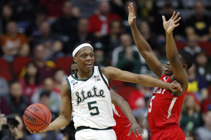 Michigan State guard Cassius Winston passes around Bradley guard Darrell Brown, right, during a first round men's college basketball game in the NCAA Tournament, Thursday, March 21, 2019, in Des Moines, Iowa. (AP Photo/Charlie Neibergall)