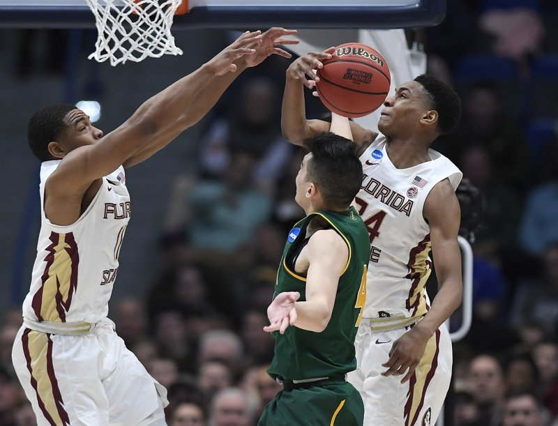 Florida State's Devin Vassell, right, blocks a shot attempt by Vermont's Robin Duncan, center, as Florida State's David Nichols, left, defends during the second half of a first round men's college basketball game in the NCAA tournament, Thursday, March 21, 2019, in Hartford, Conn. (AP Photo/Jessica Hill)