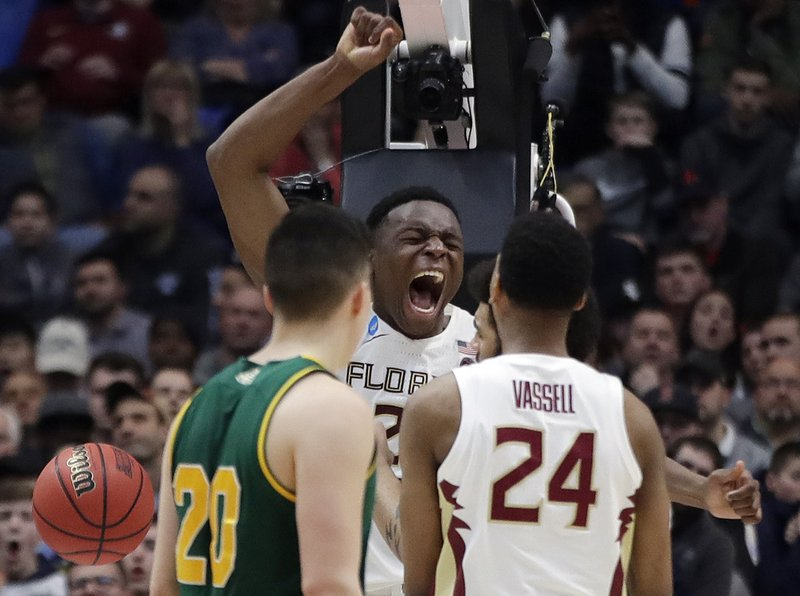 Florida State's Mfiondu Kabengele, center, celebrates after dunking the ball as Florida State's Devin Vassell (24) and Vermont's Ernie Duncan (20) look on during the second half of a first round men's college basketball game in the NCAA Tournament, Thursday, March 21, 2019, in Hartford, Conn. (AP Photo/Elise Amendola)