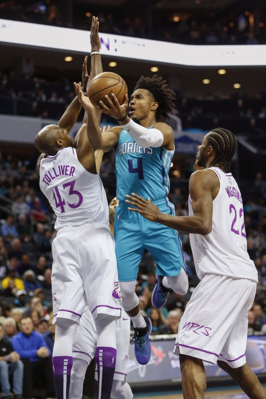 Charlotte Hornets guard Devonte' Graham (4) drives between Minnesota Timberwolves forwards Anthony Tolliver, left, and Andrew Wiggins (22) in the first half of an NBA basketball game in Charlotte, N. (AP Photo/Nell Redmond)