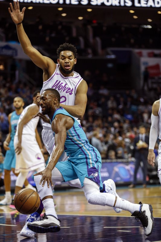 Charlotte Hornets guard Kemba Walker, front, drives into Minnesota Timberwolves center Karl-Anthony Towns in the first half of an NBA basketball game in Charlotte, N. (AP Photo/Nell Redmond)