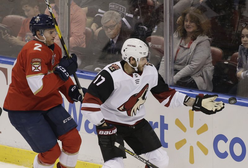 Arizona Coyotes center Alex Galchenyuk (17) stops the puck with his glove as Florida Panthers defenseman Josh Brown (2) follows during the first period of an NHL hockey game on Thursday, March 21, 2019, in Sunrise, Fla. (AP Photo/Terry Renna)
