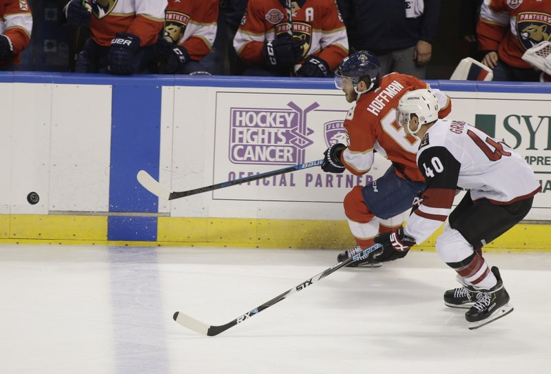 Florida Panthers left wing Mike Hoffman (68) and Arizona Coyotes right wing Michael Grabner (40) chase the puck during the first period of an NHL hockey game on Thursday, March 21, 2019, in Sunrise, Fla. (AP Photo/Terry Renna)