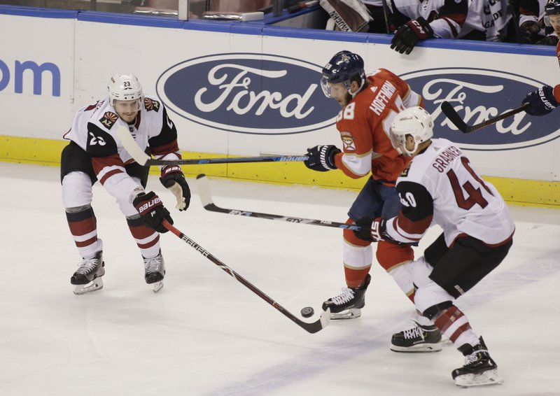 Arizona Coyotes defenseman Oliver Ekman-Larsson (23) and right wing Michael Grabner (40) battle for the puck with Florida Panthers left wing Mike Hoffman (68) during the first period of an NHL hockey game on Thursday, March 21, 2019, in Sunrise, Fla. (AP Photo/Terry Renna)