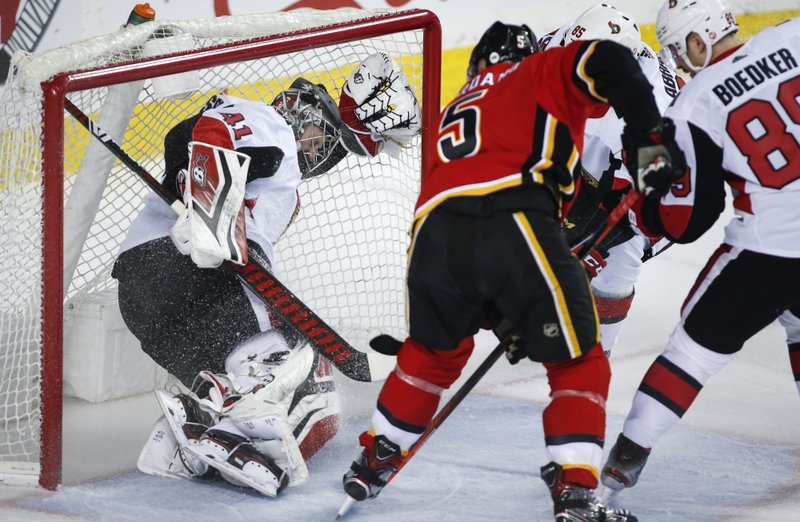 Ottawa Senators goalie Craig Anderson, left, is pushed into the net as Calgary Flames' Mark Giordano scores during first-period NHL hockey game action in Calgary, Alberta, Thursday, March 21, 2019. (Jeff McIntosh/The Canadian Press via AP)