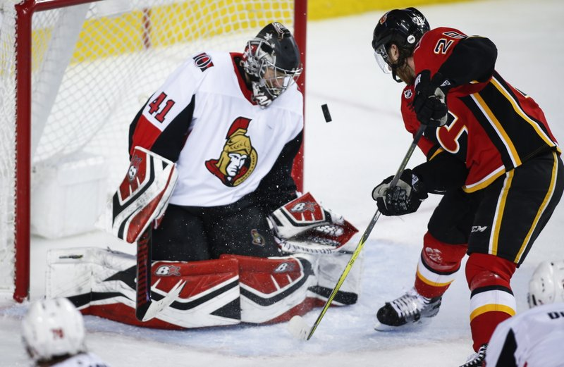 Ottawa Senators goalie Craig Anderson, left, stops a shot from Calgary Flames' Elias Lindholm during the third period of an NHL hockey game in Calgary, Alberta, Thursday, March 21, 2019. (Jeff McIntosh/The Canadian Press via AP)