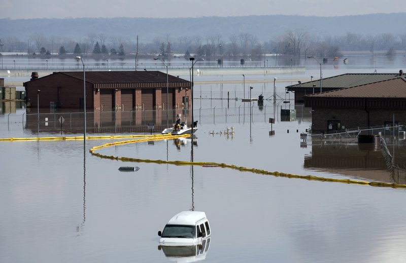 In this March 18, 2019 photo released by the U.S. Air Force, environmental restoration employees deploy a containment boom from a boat on Offutt Air Force Base in Neb. (Delanie Stafford, The U.S. Air Force via AP)